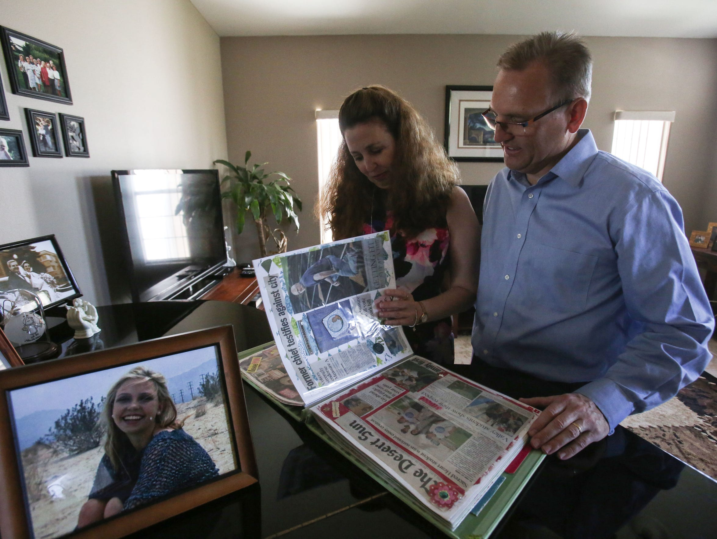 Dave and Gigi Muth flip through a scrapbook made by