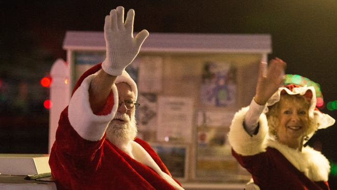 Mr. and Mrs. Santa Claus wave to a crowd during Ocean City's Winterfest of Lights on Thursday, Nov. 16, 2017.