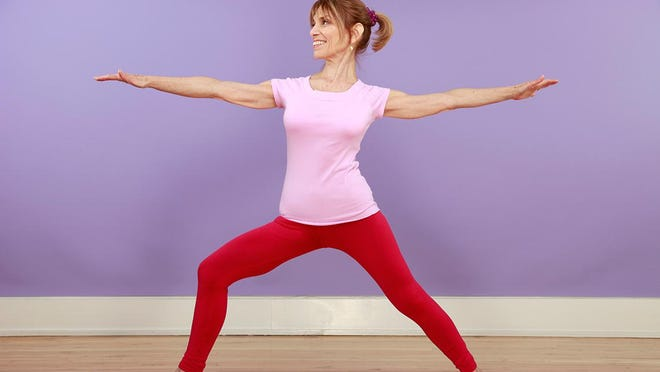 A woman demonstrates a yoga position.