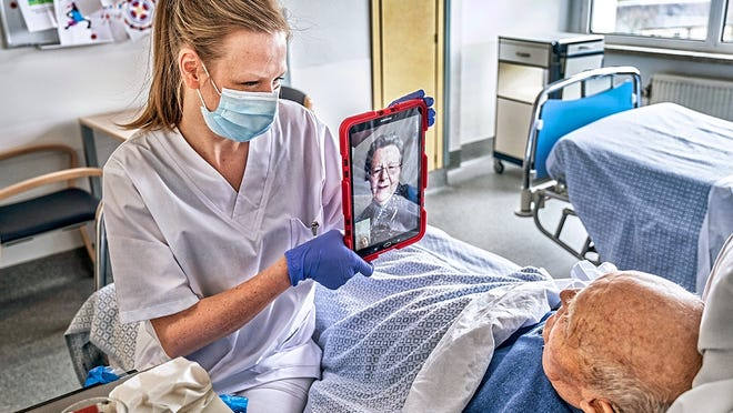 A nurse helps a nursing home resident have a virtual visit with a family member during the COVID-19 pandemic.  AARP Photo