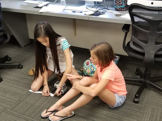 Catherine Lam (left) and Caroline Henry, participants in Our Lady of Mercy Academy's robotics camp, take measurements necessary for coding their robot to travel and park.