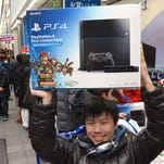 A customer reacts after buying Sony's PlayStation 4 video game console in Tokyo on February 22, 2014.