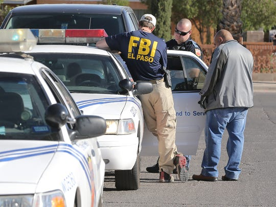 An El Paso police officer and an FBI agent talk to a man after a joint operation Tuesday in Northeast El Paso.