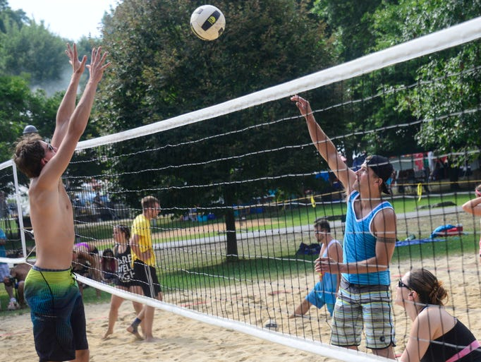 Jesse Bishop, from Johnson City, hits the ball while Alex Czopek, from Plymouth, Pa., tries to block it during a volleyball game at Otsiningo Park on Saturday.