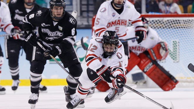 Apr 9, 2015; Boston, MA, USA; Nebraska-Omaha Mavericks forward David Pope (12) reaches for the puck in front of Providence College Friars defenseman Tom Parisi (6) during the first period of the semifinal game in the men's Frozen Four college ice hockey tournament at TD Garden. Mandatory Credit: Greg M. Cooper-USA TODAY Sports