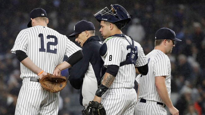 New York Yankees relief pitcher Adam Warren, right, leaves the game as New York Yankees catcher Gary Sanchez, center, and manager Joe Girardi, second from left, react during the eighth inning of a baseball game against the Boston Red Sox Wednesday, Sept. 28, 2016, in New York.