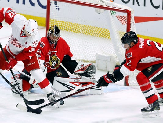 Ottawa Senators' Dion Phaneuf (2) reaches for the puck as Detroit Red Wings' Evgeny Svechnikov (37) looks on along with Senators goalie Craig Anderson (41) during the first period of an NHL hockey game in Ottawa, Ontario, Tuesday, April 4, 2017. (Fred Chartrand/The Canadian Press via AP)
