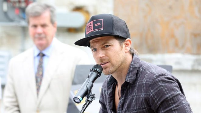 Mayor Karl Dean watches as country star Kip Moore announces his Comeback Kid Skatepark Project initiative on Buchanan Street in North Nashville.
