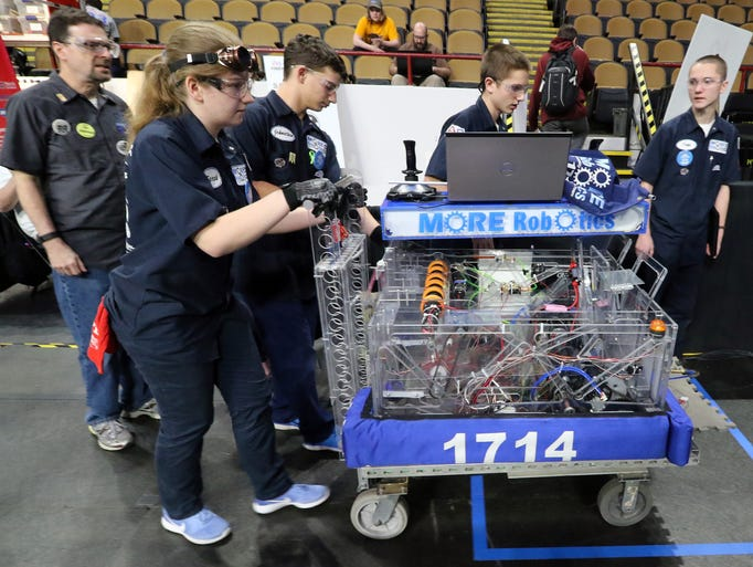 The MORE Robotics team rolls its robot into a staging