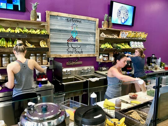 Workers at Soul Bowls in Mercato create smoothie bowls for customers one recent February afternoon.