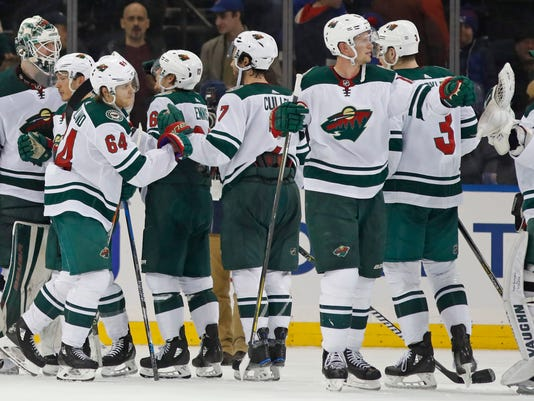 Minnesota Wild goaltender Devan Dubnyk, left, and Wild right wing Mikael Granlund, third from left, celebrate with teammates after they defeated the New York Rangers in an NHL hockey game in New York, Friday, Feb. 23, 2018. (AP Photo/Kathy Willens)