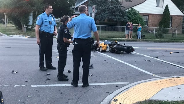 Police officers examine the scene of a car-motorcycle crash Wednesday in Lansing.
