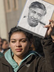 Francesca Wodja, 16, from Lansing, holds a portrait of Cesar E. Chavez during a 2010 march and a celebration of naming part of Grand River Avenue and a plaza in Old Town after the civil rights hero.