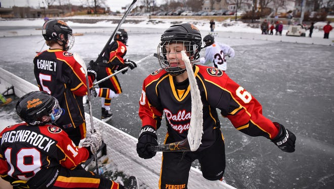 Team members of the Dallas Penguins complete a change while playing a St. Cloud Youth Hockey Association team Saturday, Jan. 30 during the 2016 Granite City Pond Hockey Championships on Lake George in St. Cloud.