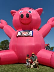 Stevie and Skip Weigle strike a pose by a giant inflatable pig during BaconFest.