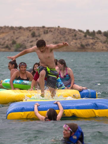 Swimmers play on inflatable structures, Thursday, April