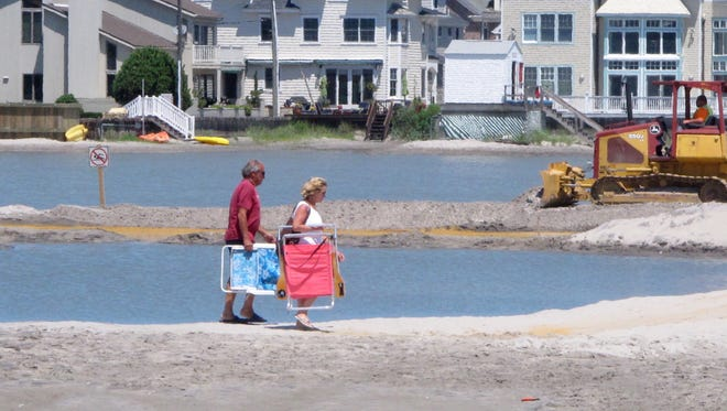 Beachgoers cross over one of numerous large pools of water that have formed on the beach in Margate N.J. due to heavy rains, Monday July 31, 2017.