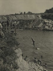 Swimmers dive into what at the time was one of Milwaukee's newest swimming spots — the beach at Estabrook Park, shown in this 1931 Milwaukee Journal photo.