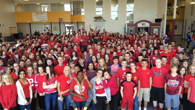 Cooper High School students gather at first lunch wearing red in honor of classmate Travis Liversgowdy Friday, May 8, 2015.