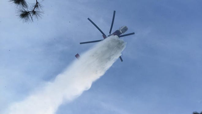 A firefighting helicopter dumps water on a fire in the Big Cypress National Preserve.
