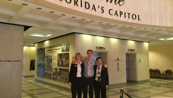 Mitch Nelson, center, and Jason McIntosh, left, received the Governor's Young Entrepreneurship Award on Tuesday at the Capitol.