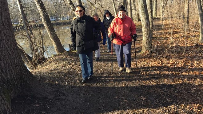 Members of the Blue Water Outdoor Club walk along the trails of East China Township Park on Dec. 20.