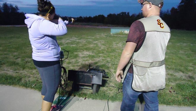 John Greaves, a 2014 Simpson College graduate, instructs a shooter during a club shoot.