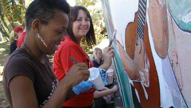 Students participating in SUU's Alternative Spring Break help to restore a mural.
