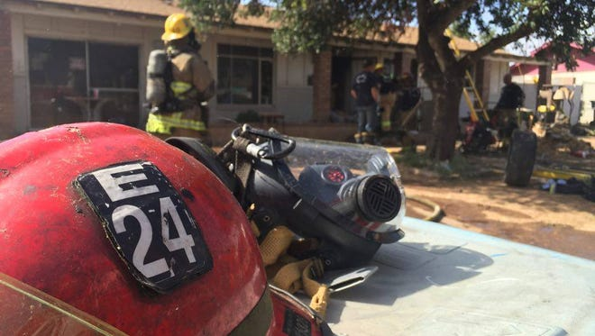 Phoenix fire crews clean up debris and remaining materials damaged in the house fire on March 15.