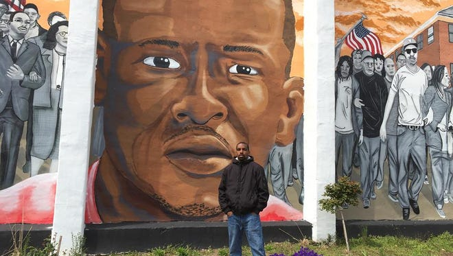 Michael Brown, 28, of Baltimore, stands in front of a mural of Freddie Gray in West Baltimore on April 11, 2016.