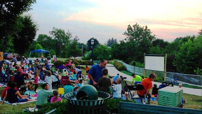 Crowd settles in to enjoy an outdoor movie on a Second Saturday event in Fort Chambers Park last summer.