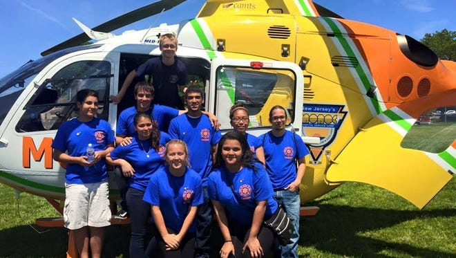 Cadets at the 2015 Bayshore EMS Cadet Competition pose in front of a medevac helicopter.