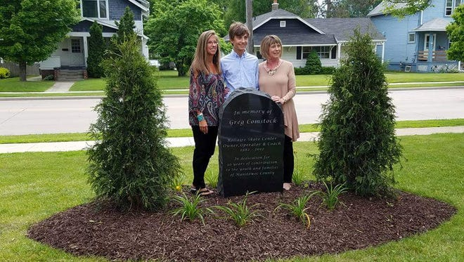 A memorial in tribute to former Rollaire owner and speed skating coach Greg Comstock was dedicated June 4 outside the rink. Pictured, from left, are Lori Comstock-Kramer, Greg's daughter; Aidan Kramer , Greg's grandson; and Cindy Comstock, Greg's wife.