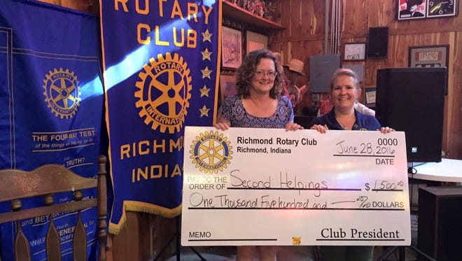 Karole Passmore, left, accepts a $1,500 donation for Second Helpings from Richmond Rotary Club's Sayward Salazar.