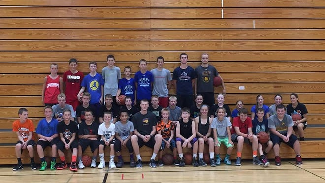 The participants pose for a picture around Paul Jesperson, who held a basketball camp last week at Menomonie Middle School.