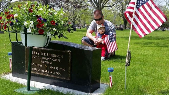 Jeremy Peterson and his son, Sage, visit the grave site of Peterson's father, Jerry Peterson, who took his own life. He was a Vietnam War veteran and received three Purple Hearts from combat during his life.