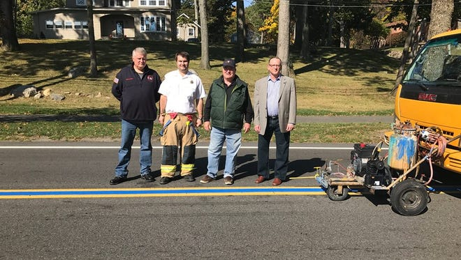 Mountain Lakes councilman (and former fire chief) Doug McWilliams, left, and Councilman John Lester, right, with former fire chief Joe Mullaney and current Chief Matt DeSantis, as they celebrate a blue line honoring first responders being painted on the Boulevard on Oct. 17.