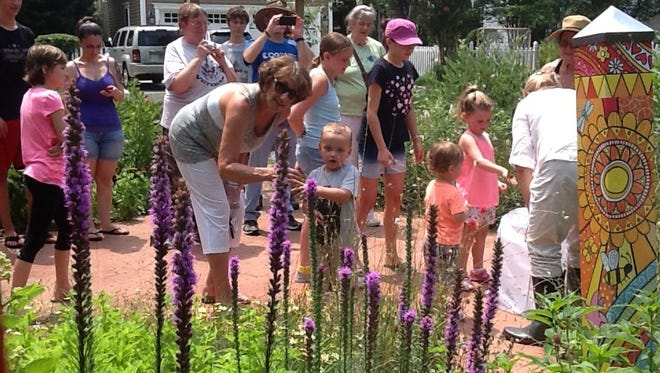 Visitors marvel at the flowers that attract butterflies at the dedicatiion of a new garden named for them in Still Park in Medford thanks to the Pines Garden Club.