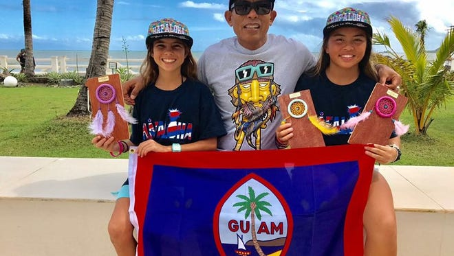 Minami Cramer, left and Angel'Lea Aguilar, right, take a photo with their coach Joe Villatora after competing in4th Philippine Wahine Classic on Nov. 19 and 20 in Baler Aurora, Philippines .