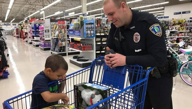"""Camron Willams, 4, shows Clay Township Patrol Officer James Pelletier the toy he picked out at  """"Christmas with a Cop"""" on Wednesday, Dec. 7, 2016."""
