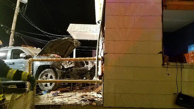Firefighters were able to rescue a man who was pinned against an inside wall after a Jeep crashed into his home.