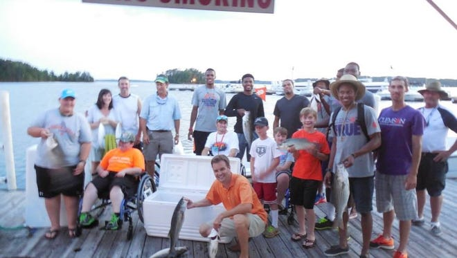 Children hold up their catches on fishing trip provided by the Outdoor Dream Foundation and the Clemson men's basketball team during summer 2015.