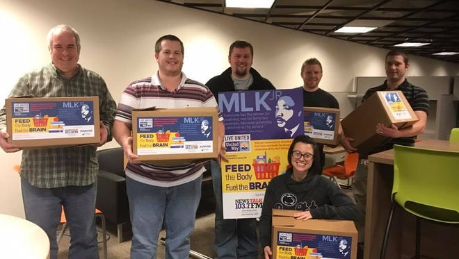 Staff in the Tactical Purchasing Department at JLG show off boxes filled with food donated to United Way's food and book drive.