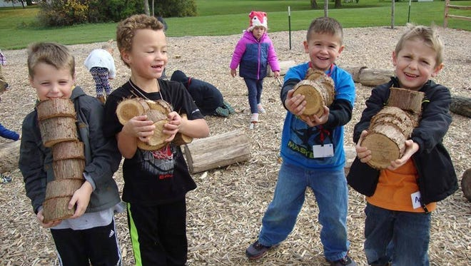 File - Boys with tree cookies at the Riverview Kindergarten and Early Learning Center Learning Adventure Land in Manitowoc.