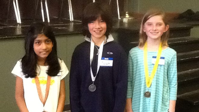 The third-grade spelling bee champions are, from left,  Sanaah Saraogi in third place, Noah Sava in second place, and Lily Novak in first place.