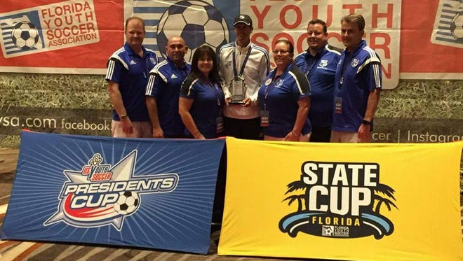 Eddie Carmean, center, and several Cape Coral Soccer Association coaches were honored in Orlando after being named the top organization in Florida.