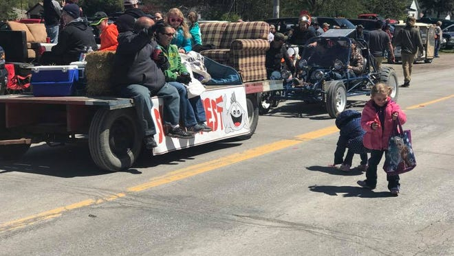 Children pick up candy tossed from one of the floats at the Suckerfest Parade on May 7, 2017.