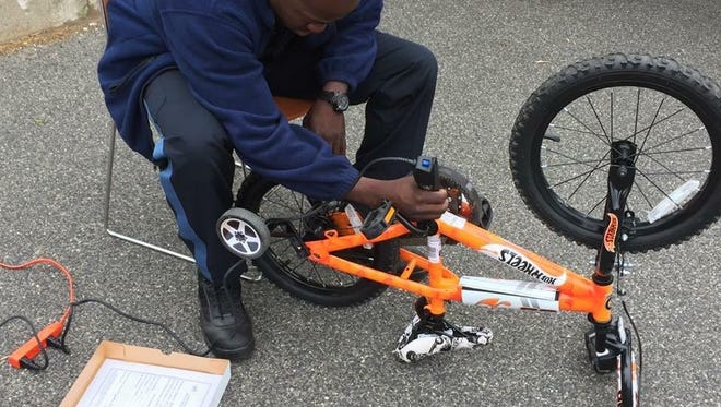 Officer Andelson Mindest, etching a child's bicycle with a registration number, which is kept on file in the Lodi Police Department in the event of theft.