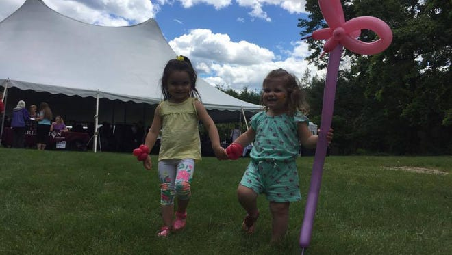 Arielle Montgomery (left) and Harper Hoffnagle (right) stroll out of A Taste of Arlington with their balloon animals. They said they liked the macaroni cheese and hot dogs.