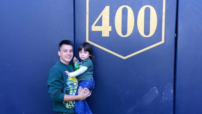 Kyle Lesniewski and his daughter, Layla, stand against the outfield wall at Miller Park in Milwaukee.